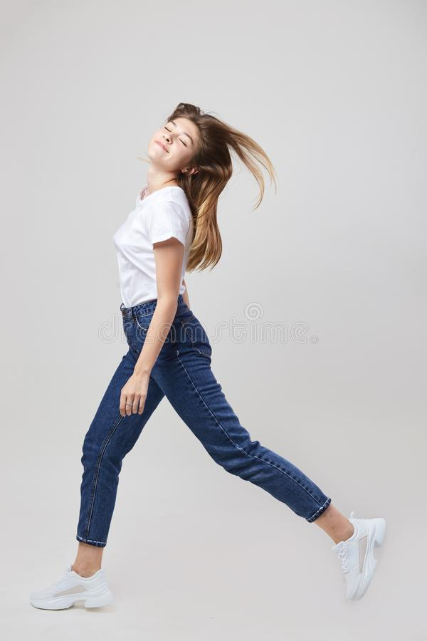 Happy girl dressed in a white t-shirt and jeans walks in the studio on a white background stock images