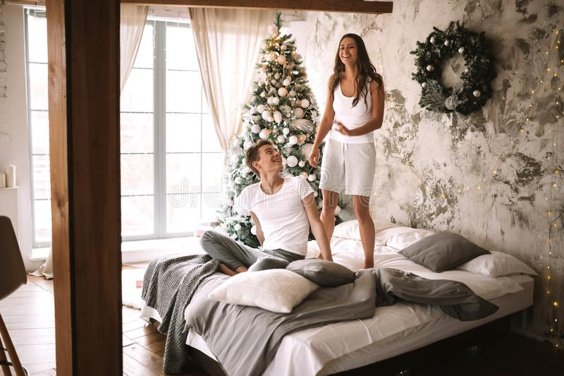 Happy girl dressed in white t-shirts and shorts is jumping on the bed next to the guy sitting there in a cozy decorated. Room with a New Year tree, gifts and stock photos