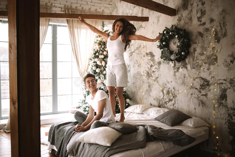 Happy girl dressed in white t-shirts and shorts is jumping on the bed next to the guy sitting there in a cozy decorated. Room with a New Year tree, gifts and royalty free stock photos