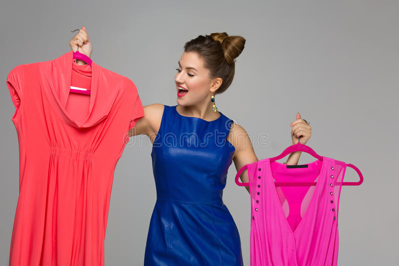 Happy girl with dresses. Beautiful happy woman holding two dresses on hangers. Price tags. Over grey background. Copy space stock image