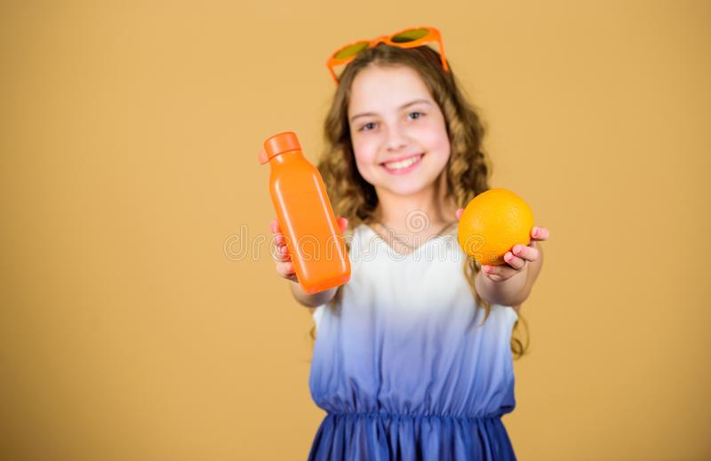 Happy girl drink fresh orange juice. summer vacation. little girl in fashion glasses. Vitamin nutrition. refreshing stock images