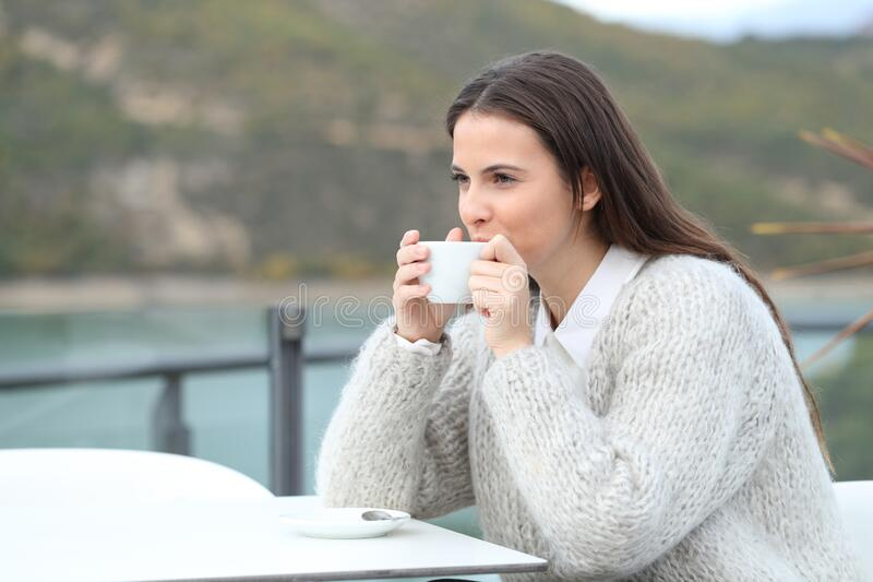 Happy girl drinking coffee looking away in a terrace royalty free stock photo