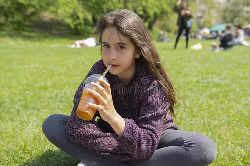 Girl drinks ice cold drink in the park stock images