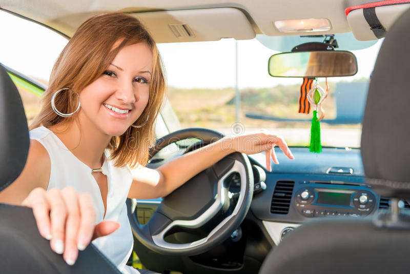 Happy girl driver behind the wheel of the car royalty free stock image
