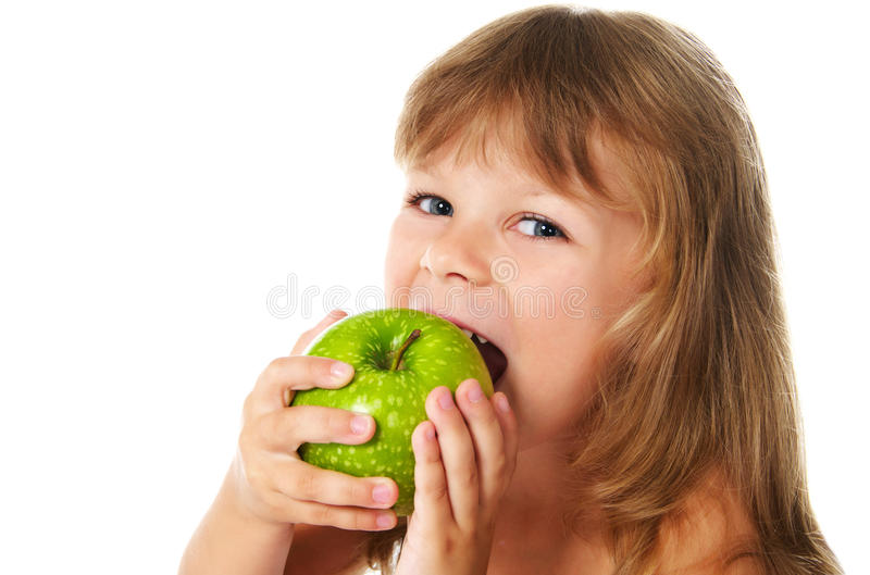 Happy girl eating green apple royalty free stock photography