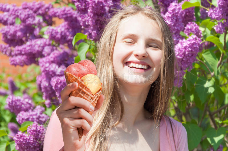 Happy girl eating ice cream outdoors royalty free stock image