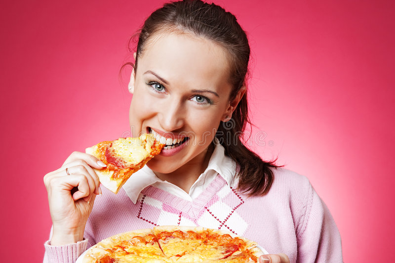 Happy girl eating pizza. Over pink background royalty free stock photo