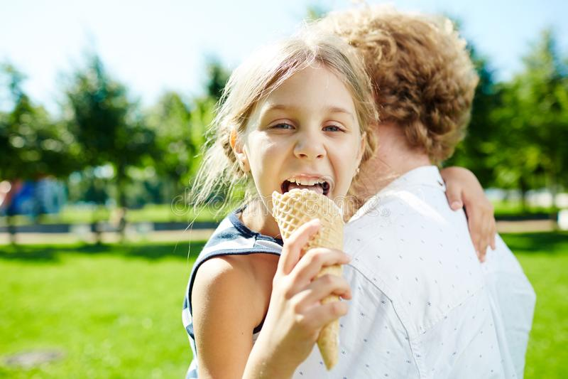 Girl with ice-cream. Happy girl eating tasty ice-cream on her father hands during walk in park stock photography