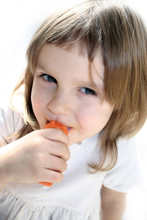 Happy girl eats carrot royalty free stock image