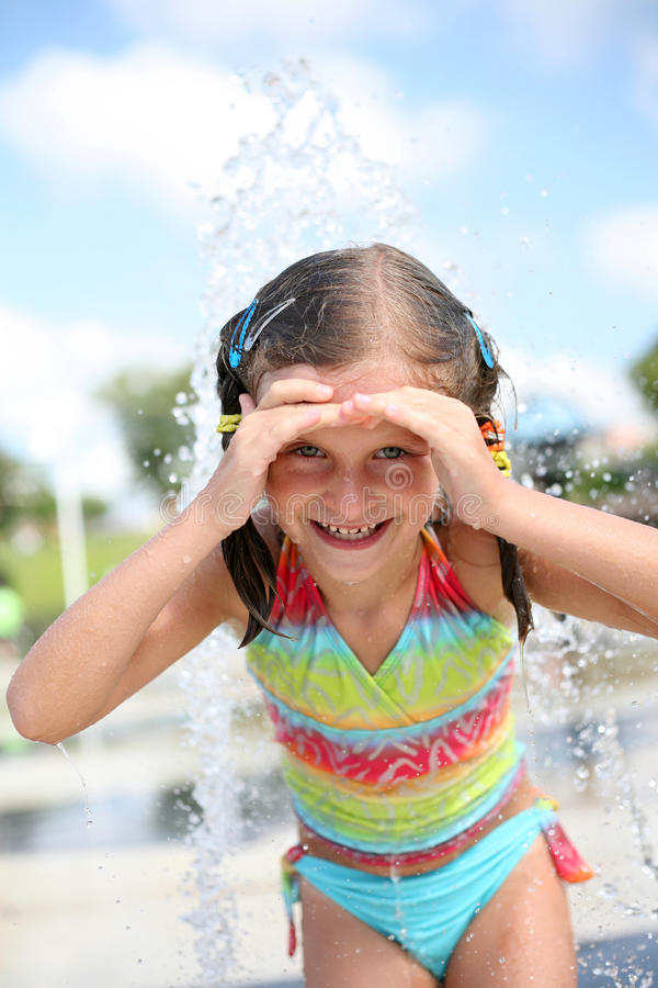Happy girl enjoys summer day at swimming pool. royalty free stock photography