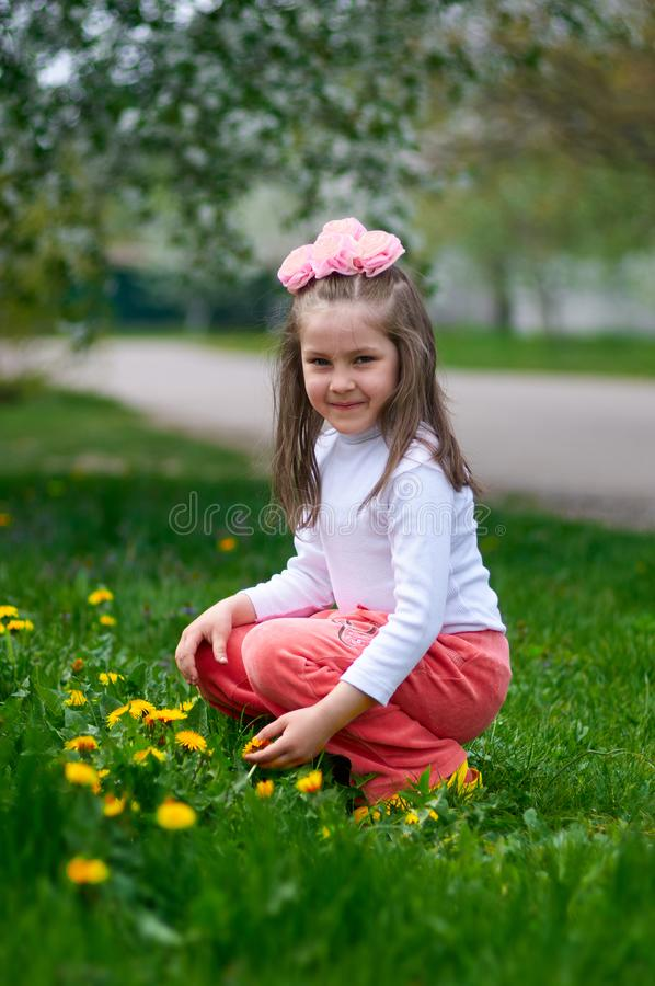 Happy girl enjoys summer time in a dandelion meadow stock image