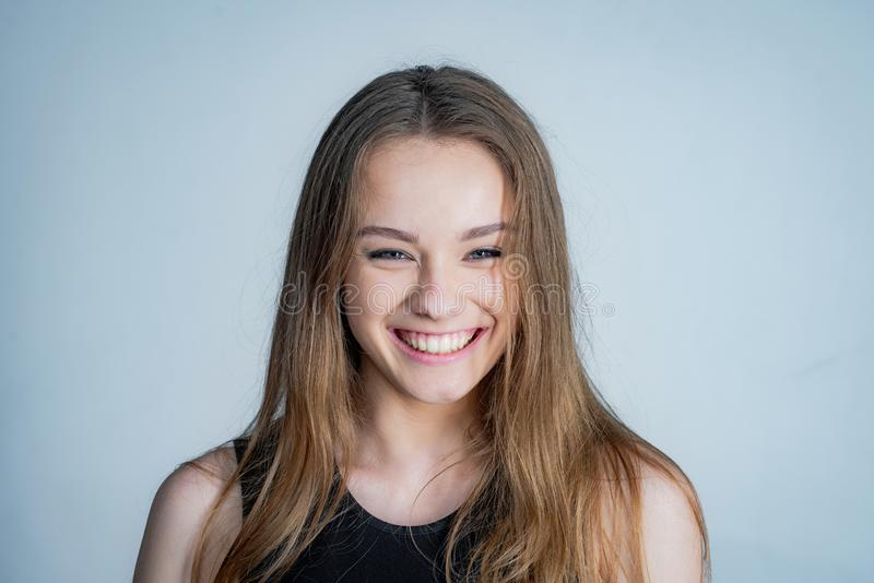 Happy girl face portrait. Close up portrait of young cheerful beautiful girl with long hair in casual shirt smiling stock image
