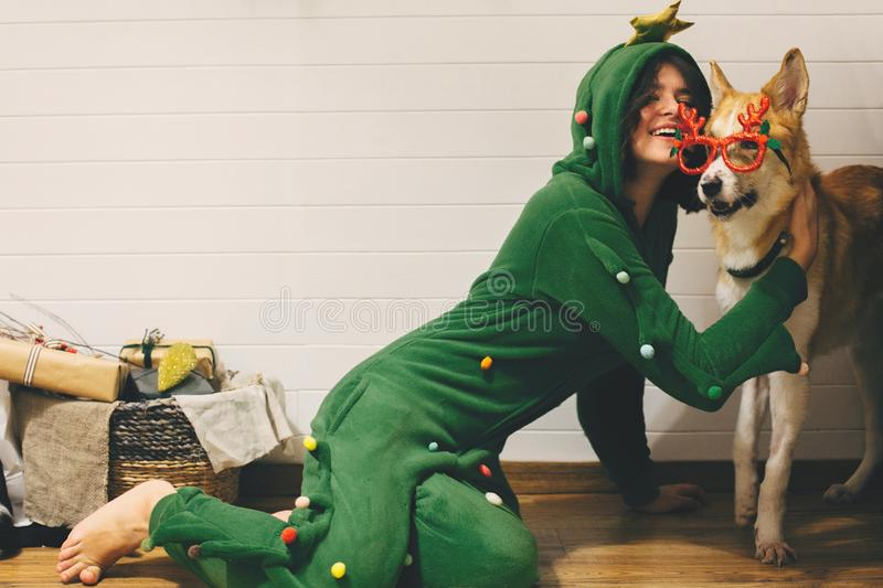 Happy girl in festive pajama hugging dog in holiday glasses with deer horns, sitting on floor with christmas presents in stylish stock photo