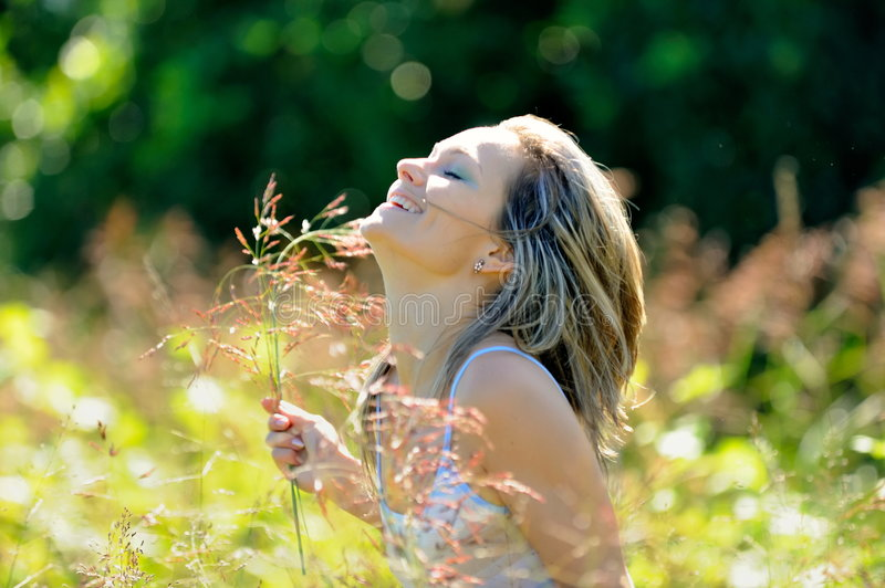 Happy girl on field in summer stock photography