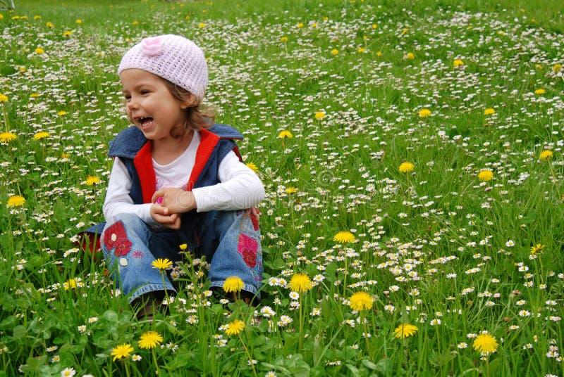 Happy girl in flower meadow royalty free stock photo
