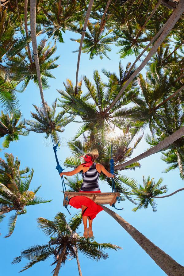 Happy girl flying up high on swing among palms stock photo