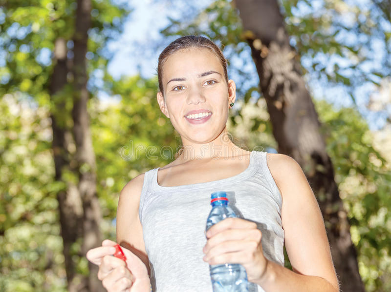 Happy girl in forest holding bottle of water stock photos