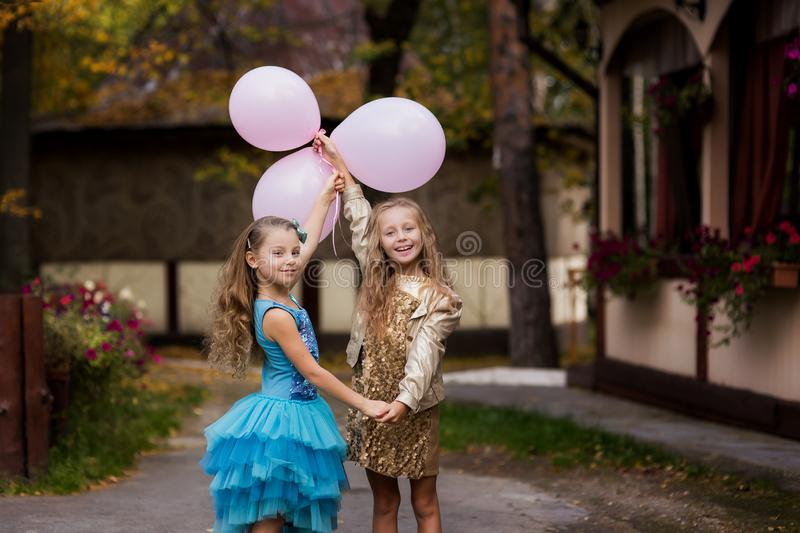Happy girl friends at a birthday party with balloons. Portrait of beautiful girlfriends royalty free stock image
