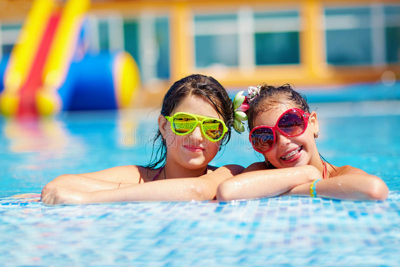 Happy girl friends enjoy swimming in the pool royalty free stock photography