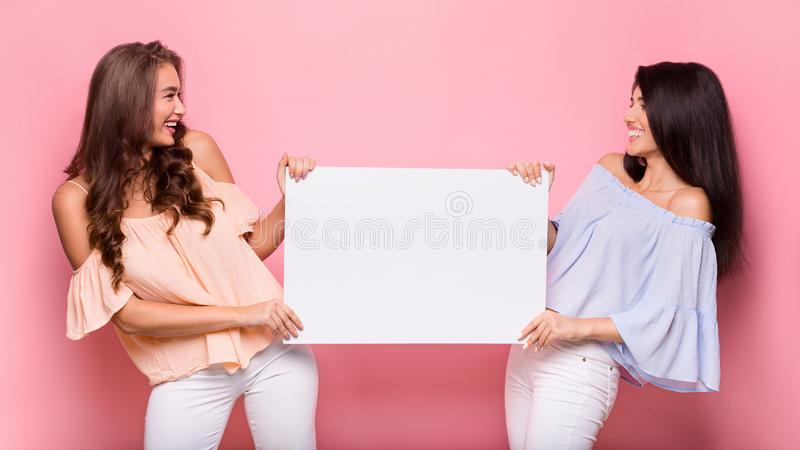 Happy girl friends holding blank advertisement board. Cheerful women holding blank advertisement sheet and smiling to each other, pink studio background, copy stock photography