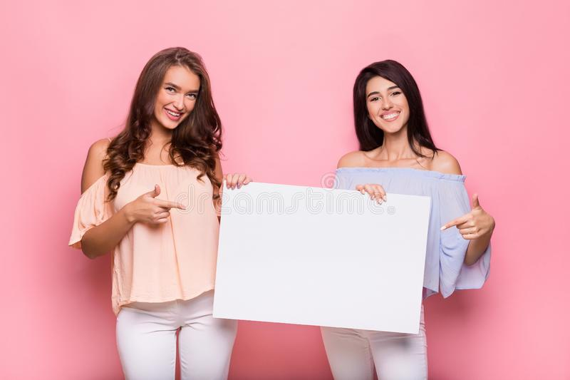 Happy girl friends holding blank advertisement board royalty free stock image