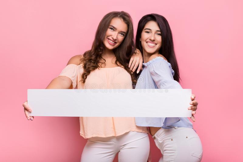Happy girl friends holding blank advertisement board stock image