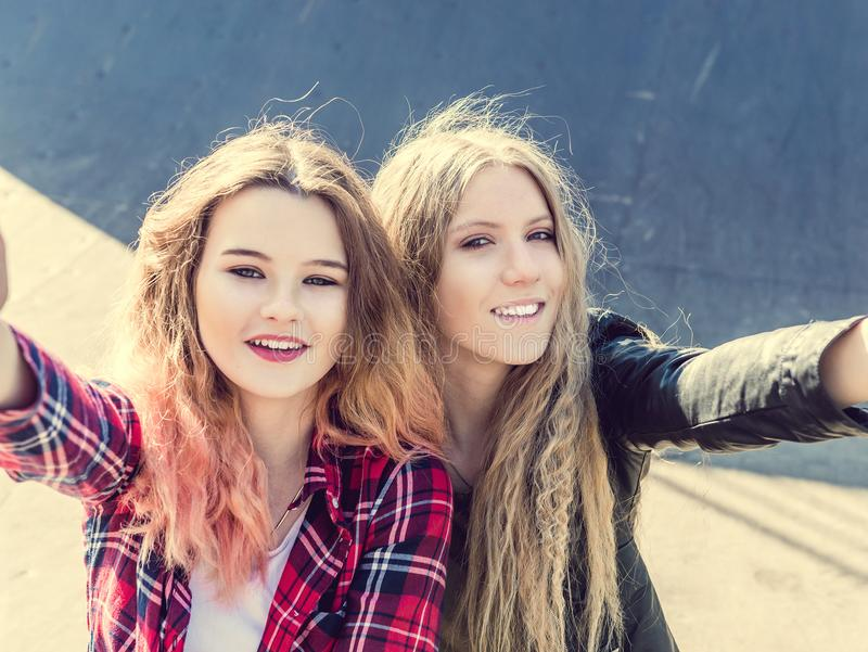 Happy girl friends taking a selfie on a summer day stock photo