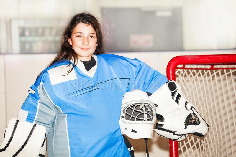 Happy girl goaltender posing after hockey match. Portrait of happy teenage girl goaltender, standing next to the net and holding helmet in her hand after hockey stock images