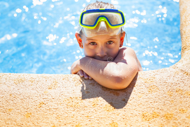 Happy girl with goggles in swimming pool stock photos