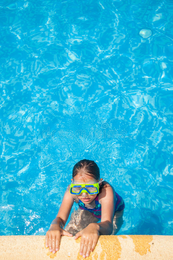 Happy girl with goggles in swimming pool stock photography