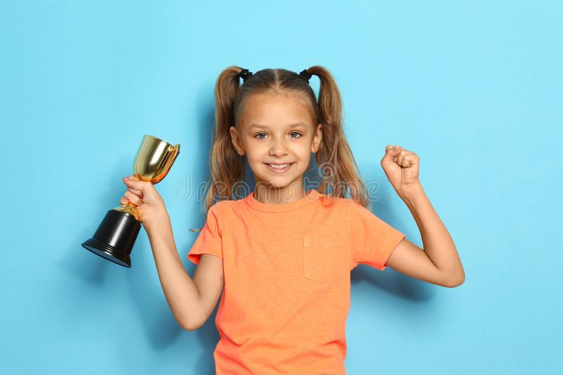 Happy girl with golden winning cup on  background. Happy girl with golden winning cup on blue background royalty free stock photo