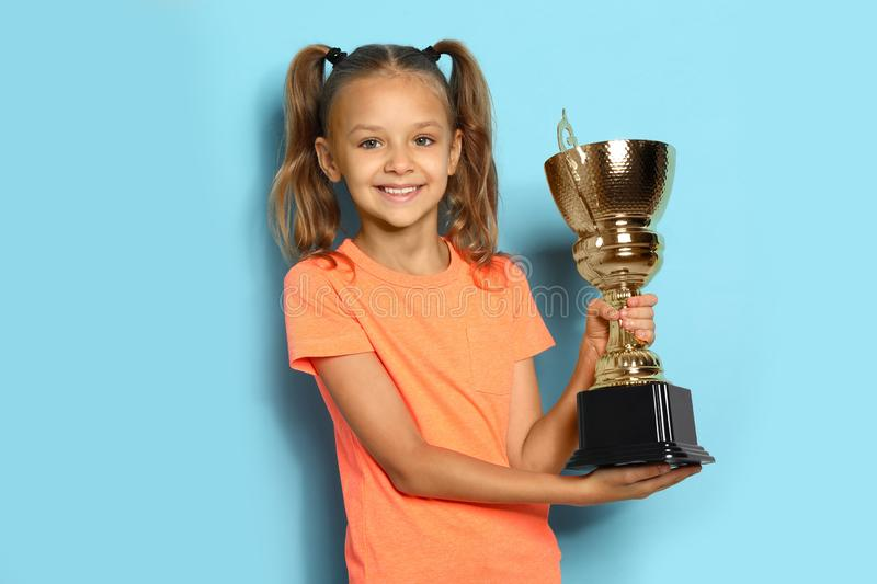 Happy girl with golden winning cup on blue backgrund. Happy girl with golden winning cup on blue background royalty free stock images
