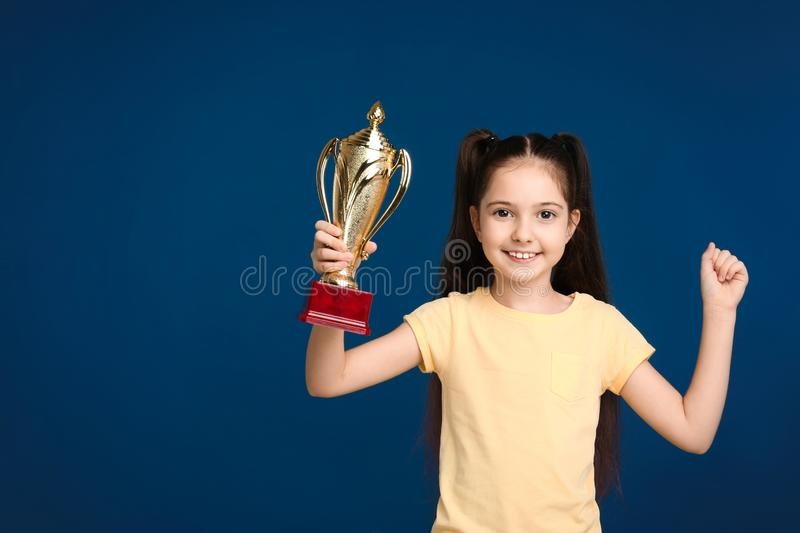 Happy girl with golden winning cup on dark blue background. Space for text royalty free stock photo