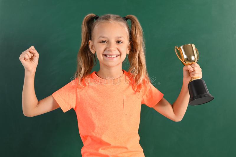 Happy girl with golden winning cup. Near chalkboard stock images