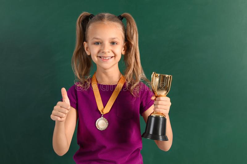 Happy girl with golden winning cup and medal. Near chalkboard stock images