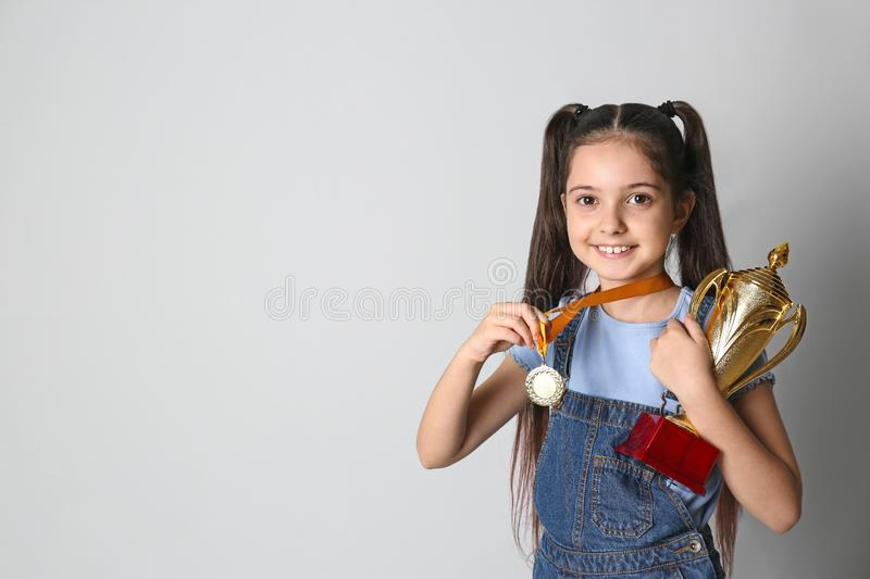 Happy girl with golden winning cup and medal on light background. Space for text stock image