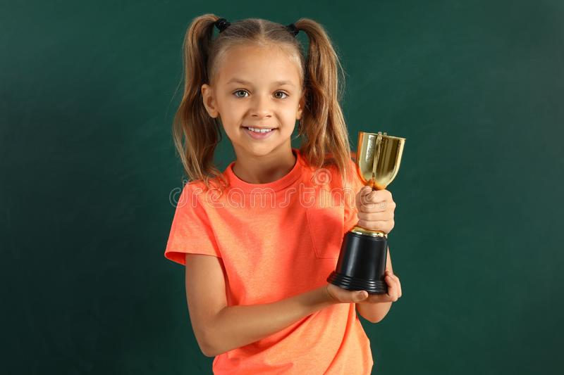 Happy girl with golden winning cup. Near chalkboard royalty free stock images