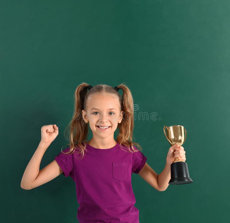Happy girl with golden winning cup. Near chalkboard royalty free stock photography