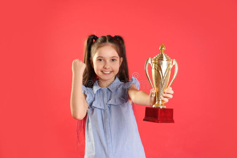 Happy girl with golden winning cup. On red background stock images