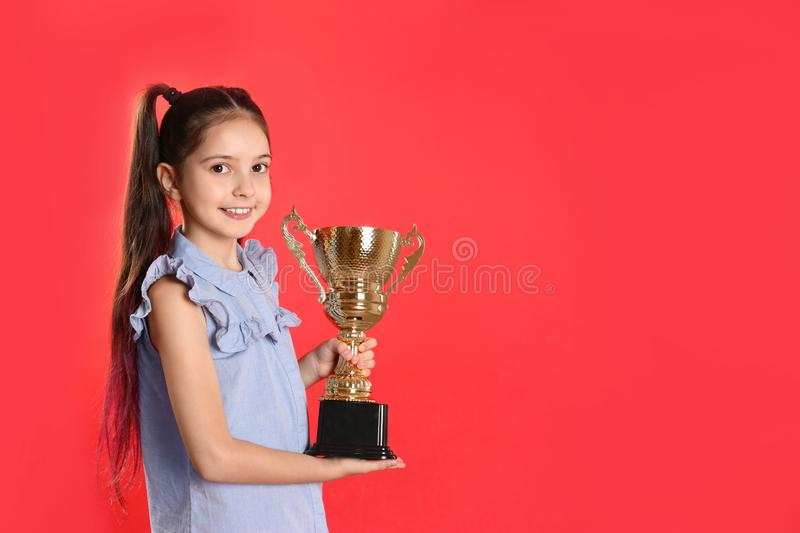 Happy girl with golden winning cup. Space for text. Happy girl with golden winning cup on red background. Space for text stock photo