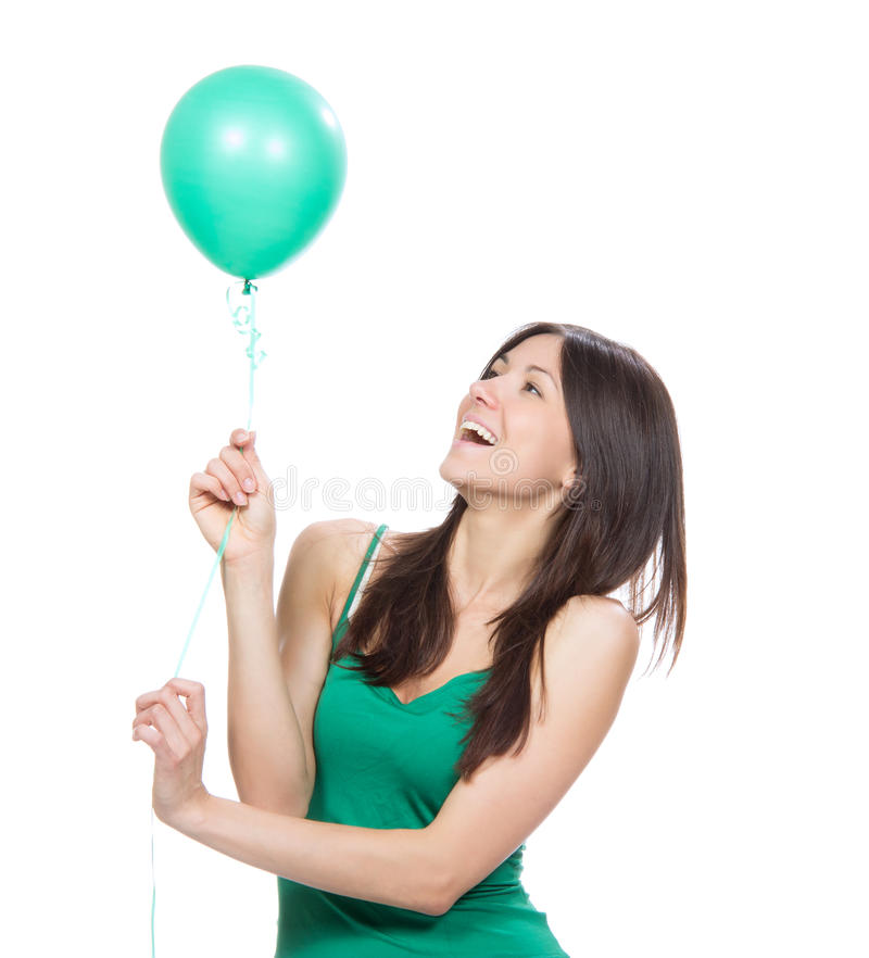 Happy girl with green balloon as a present for birthday party. Young happy girl with green balloon as a present for birthday party smiling on a white background royalty free stock photography