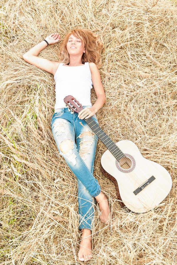 Happy girl with guitar lying on grass in meadow. royalty free stock images