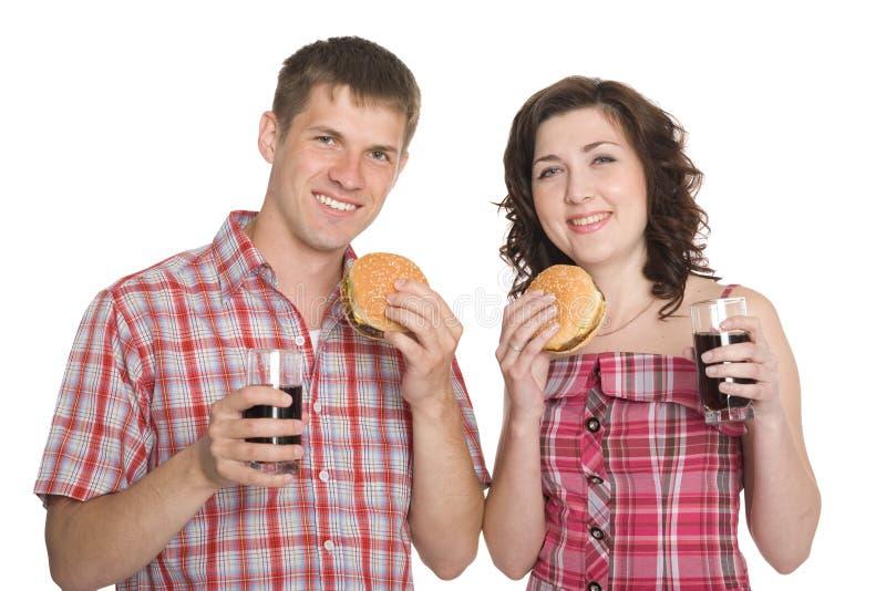 Happy Girl And A Guy Eating Hamburgers Royalty Free Stock Photos