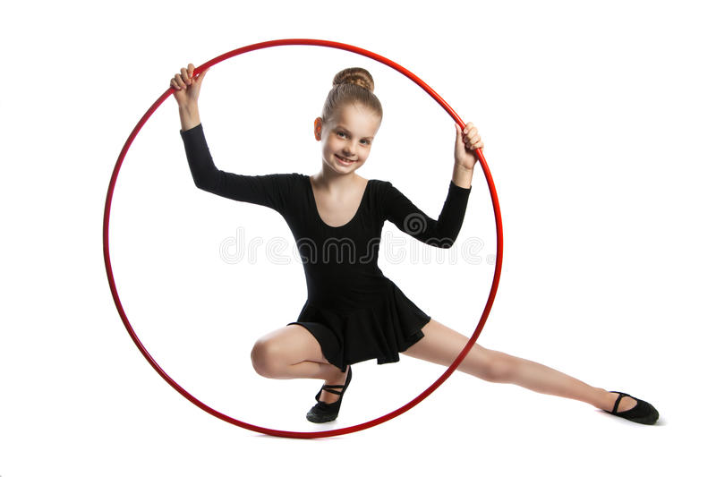 Happy girl gymnast with a hoop. Nine years old gymnast with a hoop isolated on a white background. Girl sitting on the floor with a gymnastic hoop stock photos