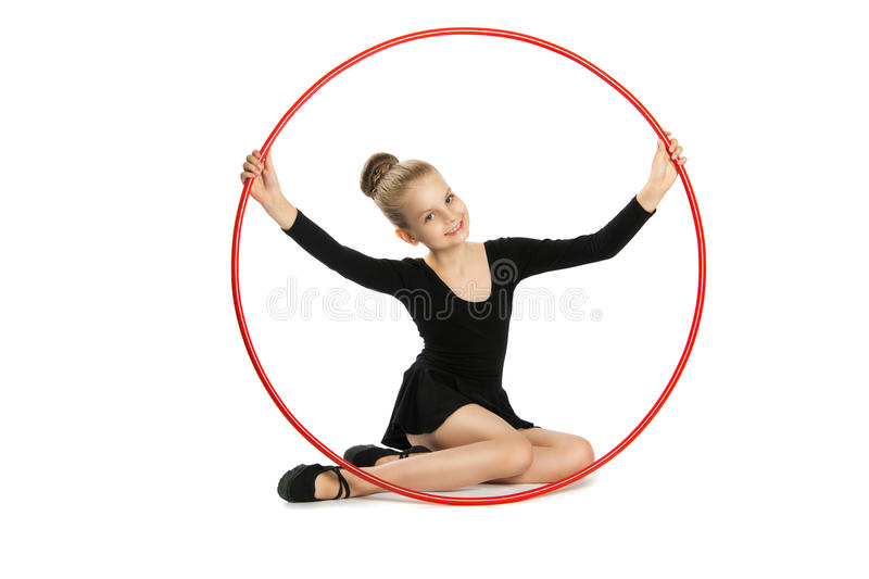 Happy girl gymnast with a hoop. Nine years old gymnast with a hoop isolated on a white background. Girl sitting on the floor with a gymnastic hoop stock image