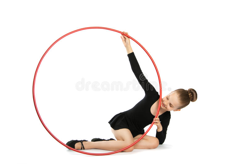 Happy girl gymnast with a hoop. Nine years old gymnast with a hoop isolated on a white background. Girl sitting on the floor with a gymnastic hoop stock photo