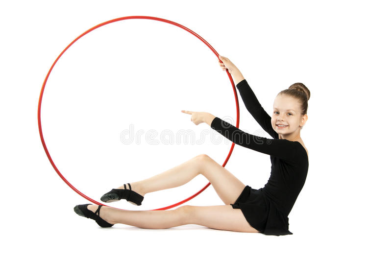 Happy girl gymnast with a hoop. Nine years old gymnast with a hoop isolated on a white background. Girl sitting on the floor with a gymnastic hoop royalty free stock photo