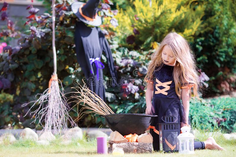 Happy little witch outdoors on Halloween. Trick or treat. Happy girl in halloween costume with jack pumpkin.Trick or treat stock photography