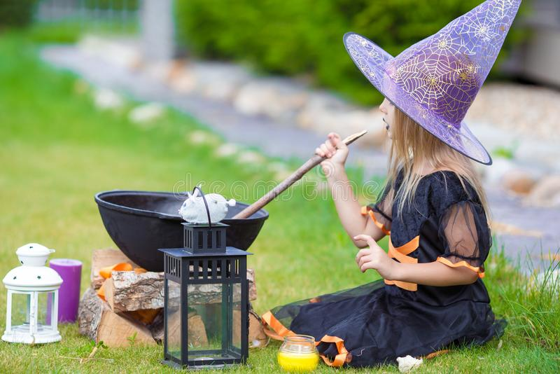 Happy little witch have fun outdoors on Halloween. Trick or treat. Happy girl in halloween costume with jack pumpkin.Trick or treat royalty free stock image