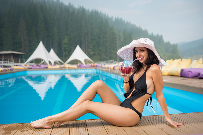 Happy girl in a hat sitting on the edge of swimming pool and drinking cocktail on the background of mighty forest. Young happy girl in a hat and black bikini royalty free stock image
